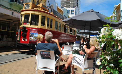 People relax at cafe as Christchurch Tram goes past
