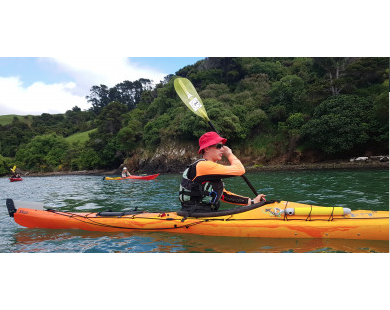 {Person in single kayak on the sea in front of cliffs and bay of Lyttelton Harbour