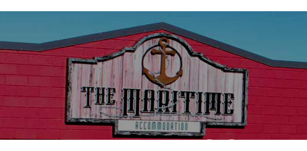 Image of the sign saying The Maritime with an anchor and rope logo at the top. pink background to the wooden sign