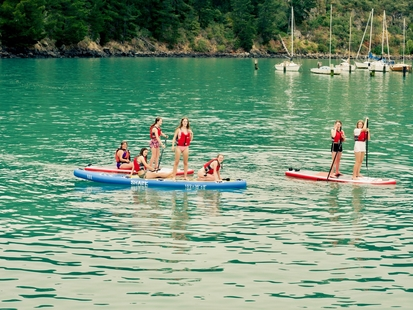 green sea with 3 paddle boards and 7 people sitting and standing on them with boats in the background