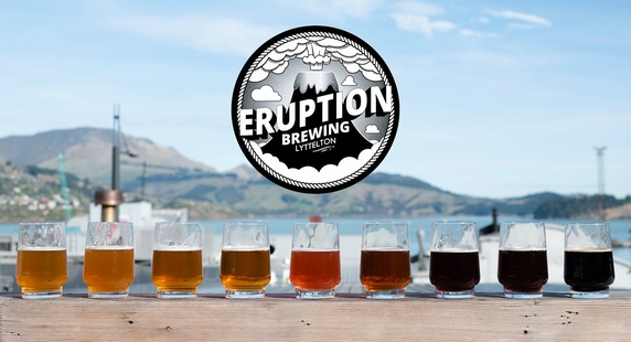 A line of glasses in front of Lyttelton Harbour with a logo for eruption brewery