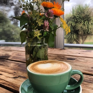 cup of coffee in front of a jar of flowers