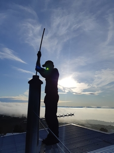 Image of man cleaning a chimeny with the Lyttelton harbour for harbour side fires